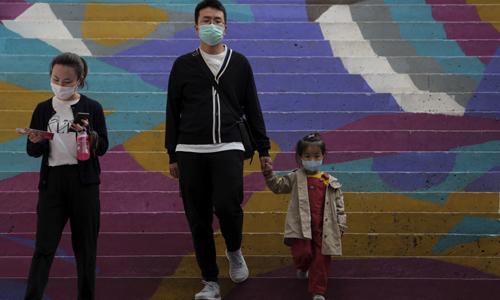 11일 베이징의 한 거리에서 마스크를 쓴 한 가족이 계단을 걸어 내려오고 있는 모습. 베이징=AP연합뉴스