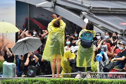 방콕 시내 시위 참석자들이 다른 시위대로부터 수신호를 배우고 있다. 2020.10.18 [AFP=연합뉴스]