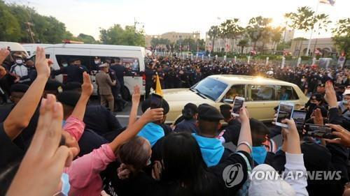 수티다 왕비가 탄 차량을 향해 세 손가락 경례를 하는 시위대 [로이터=연합뉴스. 재판매 및 DB 금지]