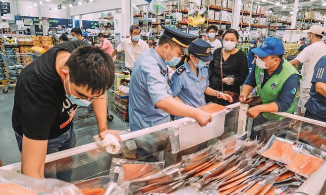 중국 국가식품의약품감독관리총국 관계자가 지난 6월 베이징의 한 대형마트에서 판매되는 연어를 검사하고 있다. 글로벌타임스
