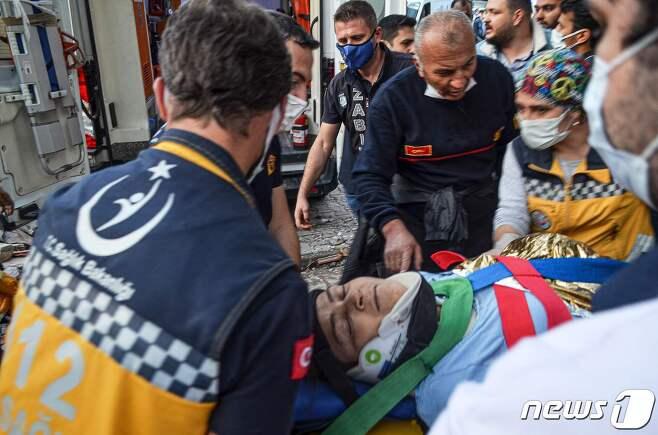 구조대원들이 지진으로 부상당한 시민들을 옮기고 있다. © AFP=뉴스1