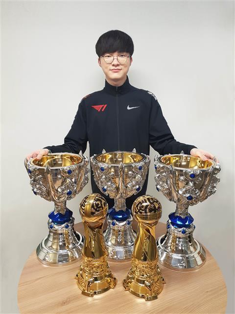 이상혁이 3일 T1 숙소에서 리그오브레전드 월드 챔피언십 트로피를 앞에 두고 기념 촬영을 하는 모습.T1 제공