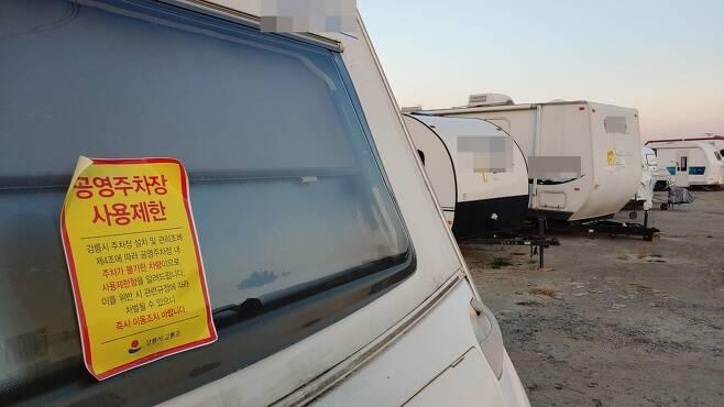 강원 강릉시가 공영 주차장을 장기간 차지하고 있는 캠핑카에 주차장 사용을 제한한다는 스티커를 부착해놨다. [촬영 이해용]