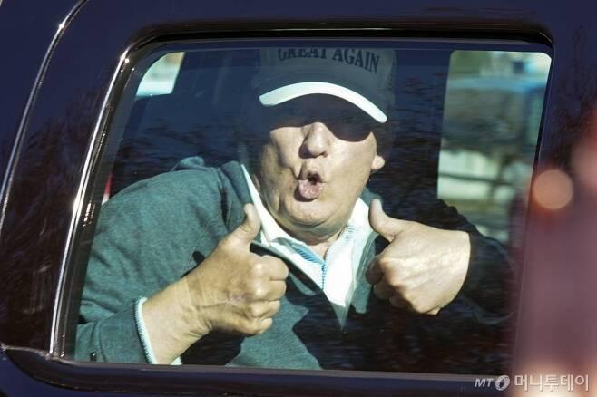 """[스털링=AP/뉴시스]도널드 트럼프 미국 대통령이 8일(현지시간) 버지니아주 스털링에 있는 트럼프 내셔널 CC에서 골프를 친 뒤 차를 타고 출발하면서 지지자들에게 엄지손가락 두 개를 치켜세우고 있다. 대선 패배를 인정하지 않는 트럼프 대통령은 여전히 """"우편투표는 사기""""라는 주장을 거듭하며 재검표 및 개표중단 소송 등 일련의 법적 조치를 계속하고 있다. 2020.11.09."""
