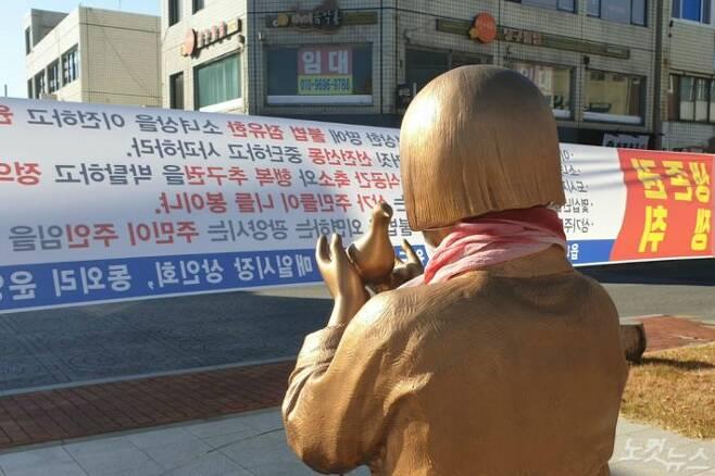 광양 평화의 소녀상이 인근 상인들의 이전 요구가 담긴 현수막을 바라보고 있다.(사진=최창민 기자)