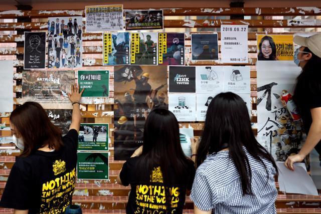 홍콩 명문 홍콩대 학생들이 9월 29일 캠퍼스 내에 마련된 이른바 '레넌 벽'에 민주화 시위를 예고하고 대만으로 밀항을 시도하다 중국 해경 당국에 체포돼 본토에 구금 중인 민주 인사 12명의 석방을 촉구하는 벽보를 붙이고 있다. 홍콩=로이터 연합뉴스