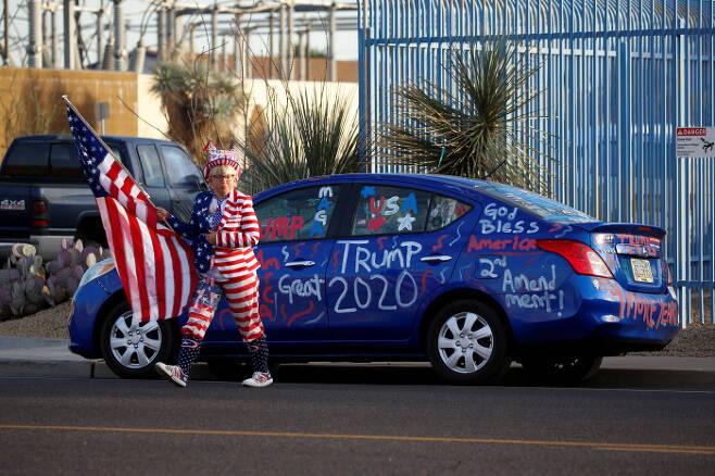 도널드 트럼프 미국 대통령을 지지하는 미국 시민이 12일(현지시간) 애리조나주 피닉스의 마리코파 카운티 개표소 앞에서 열린 '도둑질을 멈춰라' 집회에 참석하기 위해 걸어가고 있다. 피닉스|로이터연합뉴스