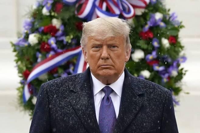 도널드 트럼프 미국 대통령이 11일(현지시간) 재향군인의 날을 맞아 버지니아주 알링턴에 있는 알링턴 국립묘지를 찾아 무명용사비를 참배한 후 비를 맞으며 돌아서고 있다. 마스크를 쓰지 않고 행사에 참석한 트럼프 대통령은 아무런 발언도 하지 않았다. 2020.11.12./사진=[알링턴=AP/뉴시스]
