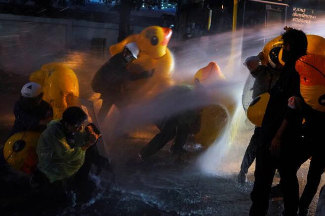 태국 현지시간으로 17일, 민주화 시위대가 대형 오리 튜브로 경찰의 물대포에 맞서고 있다(사진=로이터 연합뉴스)