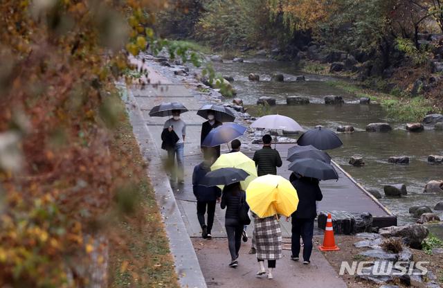 [서울=뉴시스] 조수정 기자 = 전국이 대체로 흐리고 비가 내린 지난 18일 서울 종로구 청계천에서 시민들이 우산을 들고 걸어가고 있다. 2020.11.18.  chocrystal@newsis.com