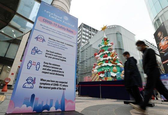 20일 서울 중구 명동 거리에 설치된 서울 빛초롱 축제 조형물 앞으로 점심시간 마스크를 쓴 시민들이 오가고 있다.   중앙방역대책본부는 이날 0시 기준으로 코로나19 신규 확진자가 363명 늘어 누적 3만17명이라고 밝혔다. 연합뉴스