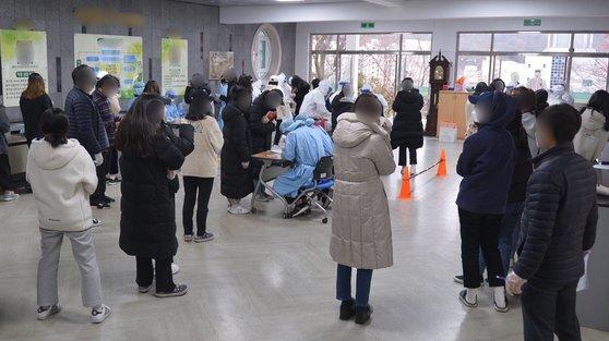 20일 오후 광주 남구 한 고등학교에서 재학생들이 진단 검사를 받기 위해 줄지어 서 있다.  이날 광주에서는 해당 학교 재학생이 진단 검사에서 양성 판정을 받았다. 뉴스1