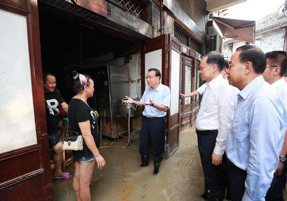 지난 8월 리커창 총리(가운데)가 충칭 수해 피해지역 주민과 이야기를 나누고 있다. 흙탕물에 발목이 잠긴 가운데 장화를 신은 리 총리의 모습. [중앙인민정부 홈페이지]
