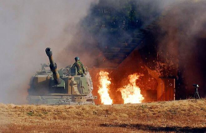 북한의 포격을 받은 해병 연평부대의 한 대원이 K-9 자주포 위에서 반격 태세를 갖추고 있다. 자주포 옆으로 불길이 번지고 부대 주변이 시커먼 연기에 휩싸였다. 세계일보 자료사진