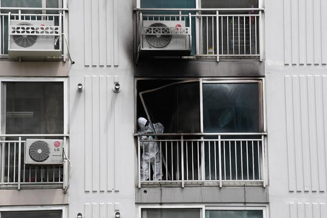 2019년 4월 17일 화재로 검게 그을린 경남 진주의 아파트에서 경찰이 현장을 조사하고 있다. 진주=진혜원 기자