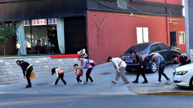 지난달 말 중국 베이징에서 CCTV 감시망을 피하기 위해 웅그린 채 걸어가는 퍼포먼스 참가자들. /BBC