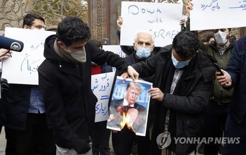 지난 28일 이란 테헤란의 외교부 앞에서 핵과학자 모센 파크리자데에 대한 테러에 항의해 도널드 트럼프 미국 대통령과 조 바이든 당선인의 사진을 태우는 학생들[EPA=연합뉴스]