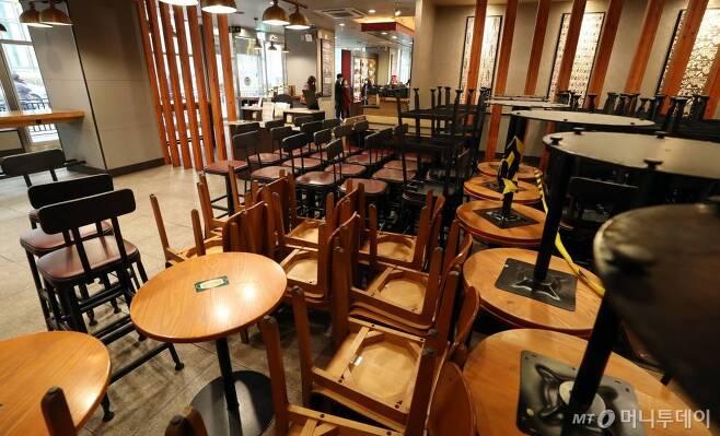 수도권 사회적 거리두기가 2단계로 격상된 24일 오전 서울 시내 한 카페에 사용 금지된 의자와 테이블이 쌓여 있다. 이날부터 카페는 영업시간과 관계없이 포장·배달만 허용되며 음식점은 저녁시간까지 정상영업을 하되 오후 9시 이후로는 포장·배달만 가능하다. / 사진=이기범 기자 leekb@