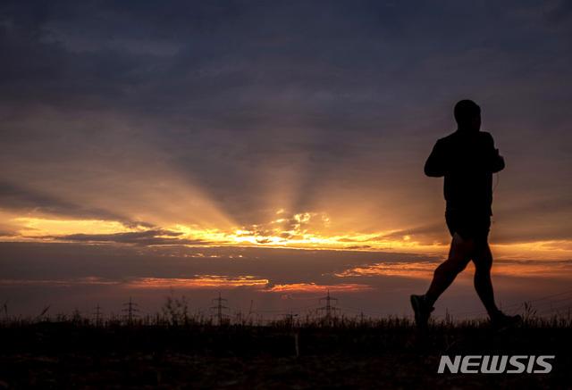 [프랑크푸르트=AP/뉴시스]13일(현지시간) 독일 프랑크푸르트에 해가 뜨는 가운데 한 남성이 프랑크푸르트 외곽의 작은 길에서 조깅 하고 있다. 2020.08.13.