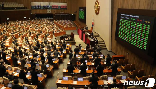 10일 오후 서울 여의도 국회에서 열린 본회의에서 공수처(고위공직자범죄수사처)법 개정안이 재석 의원 287명 가운데 찬성 187명, 반대 99명, 기권 1명으로 가결되고 있다. 국민의힘 의원들이 자리에서 일어나 피켓을 들고 구호를 외치고 있다. 2020.12.10/뉴스1 © News1 신웅수 기자