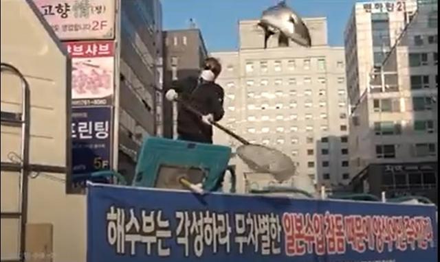 지난달 27일 서울 여의도 민주당사 앞에서 경남양식어류협회 관계자가 일본산 활어 수입에 항의하기 위해 살아 있는 참돔과 방어를 길바닥에 던지는 퍼포먼스를 하고 있다. 미래수산TV 캡처