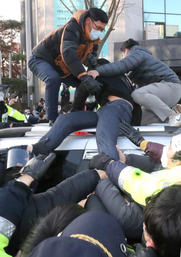아동 성범죄자 조두순(68) 출소일인 12일 오전 일부 시민들이 경기도 안산준법지원센터를 나서 집으로 향하는 호송차량을 막고 있다 (사진=뉴시스)