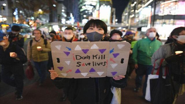 """한 참가자가 12월 6일 여성 노숙인을 추모하기 위한 촛불집회에서 """"생명을 죽이지 말고 살리라""""는 내용을 손팻말을 들고 있다. 〈마이니치신문〉"""