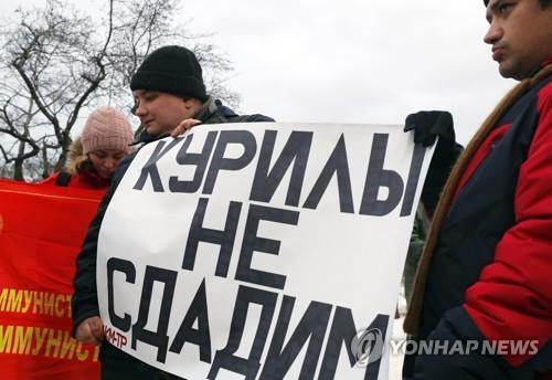 '쿠릴 절대 포기 못 한다'는 내용의 팻말을 든 러시아 공산당원. [EPA=연합뉴스]