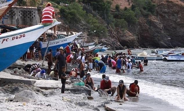 모래사장에서 보물을 찾고 있는 베네수엘라 해안 마을 주민들