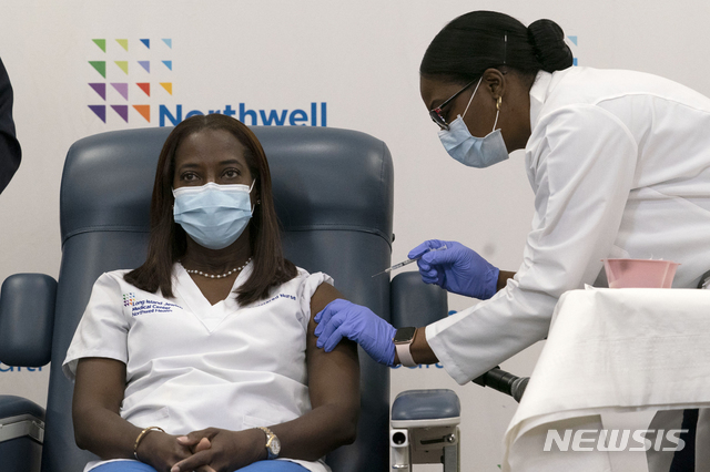 """[퀸스=AP/뉴시스] 14일(현지시간) 뉴욕 퀸스의 중환자실 간호사 샌드라 린지가 미국에서 최초로 신종 코로나바이러스 감염증(코로나19) 백신을 맞고 있다. 린지는 """"희망과 안도를 느낀다""""며 """"나는 (백신이) 이 고통스러운 시간을 마칠 시작점이길 바란다""""고 소감을 밝혔다. 2020.12.15."""