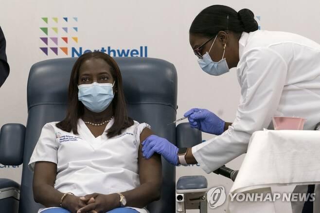 미국에서 첫 코로나19 백신 접종받는 샌드라 린지 간호사 (뉴욕 AP=연합뉴스) 미국 뉴욕시 퀸스의 롱아일랜드 주이시 메디컬 센터에서 14일(현지시간) 이 병원의 간호사 샌드라 린지가 미셸 체스터 의사로부터 화이자ㆍ바이오앤테크의 신종 코로나바이러스 감염증(코로나19) 백신을 맞고 있다. 린지 간호사는 미국의 첫 코로나19 백신 접종자로 기록됐다. sungok@yna.co.kr