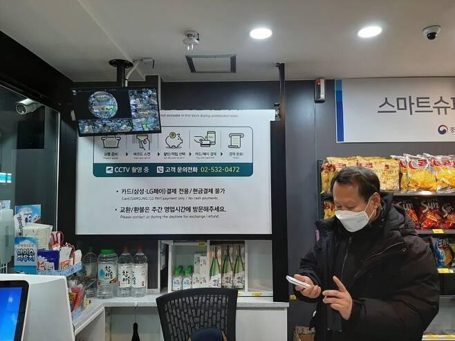 지난 14일 밤 12시 형제슈퍼 대표 최제형씨가 슈퍼를 무인으로 전환하기 위해 스마트폰 앱을 이용해 주류판매대 차단막을 내리고 있다.