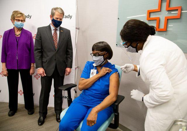 미국 조지아주 브라이언 캠프(왼쪽 두 번째) 주지사와 조지아주 공중보건국장 캐슬린 투미 박사(왼쪽 첫 번째)가 17일(현지시간) 애틀란타 그래디 병원에서 열린 기자회견에서 간호사 노마 포인덱스터가 화이자 코로나19 백신을 맞는 장면을 지켜보고 있다. EPA 연합뉴스