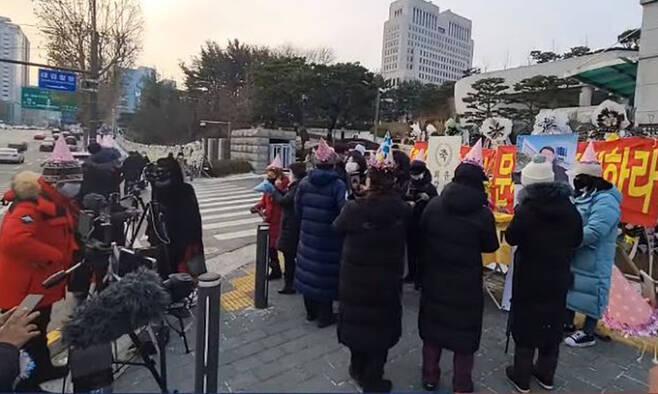 일부 보수단체 시민들이 18일 대검찰청 앞에서 고깔을 쓰고 윤석열 검찰총장 환갑 기념으로 시민들에게 떡을 돌리고 있다. 유튜브 캡처