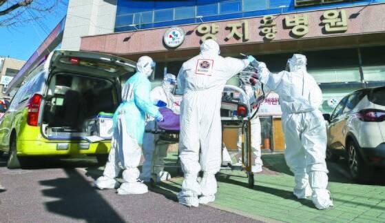 지난 17일 오후 울산시 남구 양지요양병원 앞에서 의료진과 119구급대원들이 신종 코로나바이러스 감염증(코로나19) 확진 환자를 구급차로 옮기고 있다. 연합뉴스