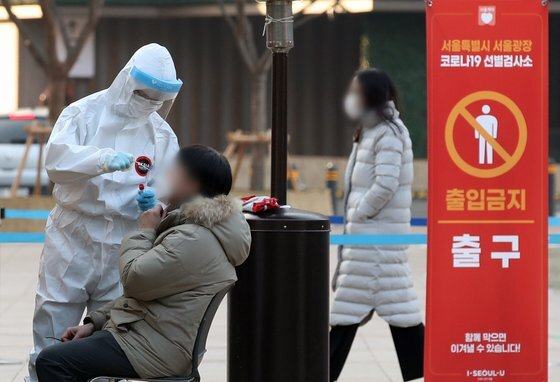 21일 서울 중구 서울시청 앞 서울광장에 마련된 신종 코로나바이러스 감염증(코로나19) 임시 선별 검사소에서 의료진이 코로나19 검체 검사를 하고 있다. 질병관리청 중앙방역대책본부는 이날 0시 기준으로 국내 코로나19 신규 확진자가 926명 늘어 누적 5만591명으로 집계됐다고 밝혔다. 이날 코로나19로 인한 사망자는 24명 늘어 현재까지 누적 사망자는 총 698명(치명률 1.38%)이다. 뉴스1