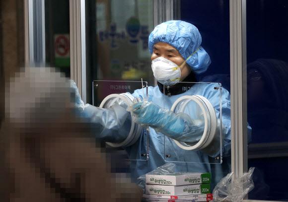 검체 채취하는 의료진 - 22일 오전 서울 관악구보건소 선별진료소에서 의료진이 신종 코로나바이러스 감염증(코로나19) 검사를 위해 검체를 채취하고 있다. 중앙방역대책본부는 이날 0시 기준으로 코로나19 신규 확진자가 869명 늘어 누적 5만1천460명이라고 밝혔다. 2020.12.22 연합뉴스