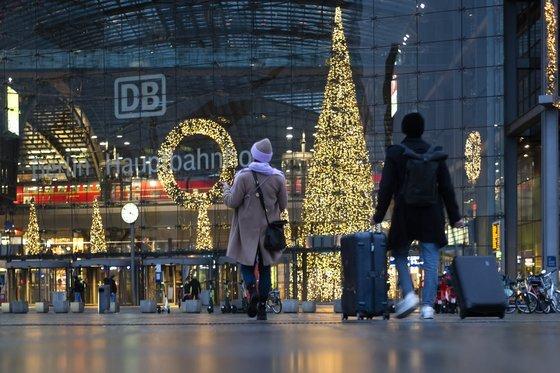 독일 베를린 중앙역 로비에 지난 23일 성탄을 축하하는 장식이 걸린 가운데 여행객들이 지나가고 있다. 방역에 따른 제한 조치로 한산하다. AP=연합뉴스