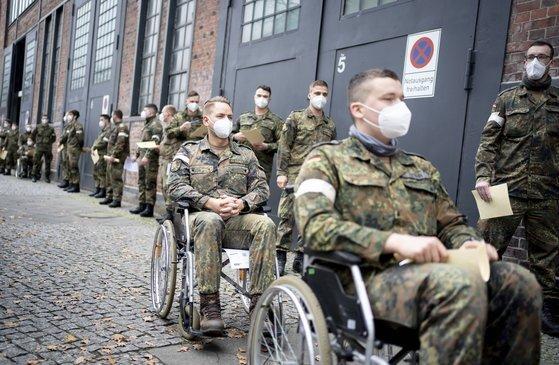 독일 연방군 군인들이 지난 23일 베를린에서 코로나 검사를 받기 위해 줄을 서있다. 독일은 27일 코로나 백신 접종을 시작할 예정이다. AP=연합뉴스