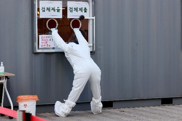 국내 신규 확진자 수가 1200명대를 기록한 25일 오후 업무에 지친 의료진 한 명이 서울 중구 서울광장에 마련된 임시선별진료소에서 검체 제출구를 붙잡고 몸을 풀고 있다. 연합뉴스