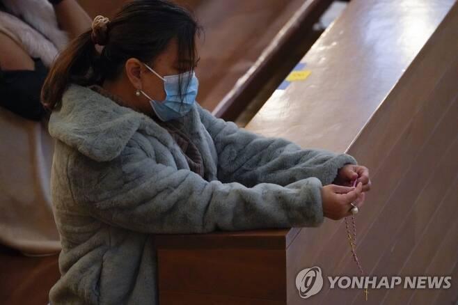 마스크를 쓴 채 크리스마스 미사에 참석한 미국 시민 [AP=연합뉴스]