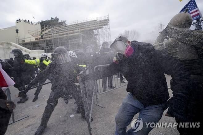 바리케이드 넘어 의사당 진입 시도하는 트럼프 지지자들 [AP=연합뉴스]