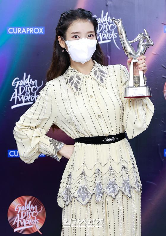 Singer IU won the grand prize in the 35th 2021 Golden Disk Awards with Curaprox digital sound recording category held at KINTEX in Goyang City, Goyang City, on the afternoon of 9th day and is performing a trophy ceremony.01. 09/