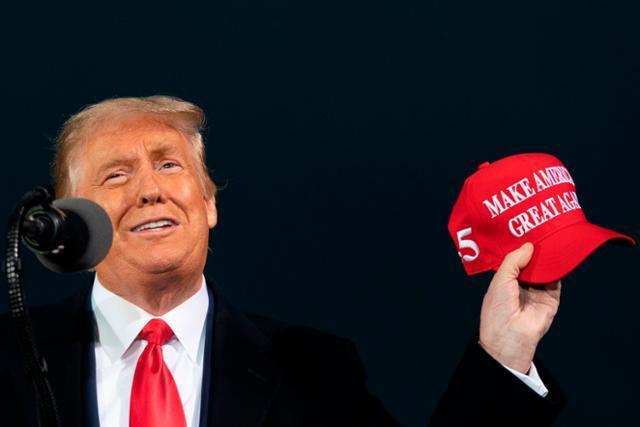 도널드 트럼프 미국 대통령이 지난해 10월 14일 아이오와주 디모인스 국제공항 대선 유세 캠페인에서 유세 구호인 '미국을 다시 위대하게(MAGA·Make America Great Again)'가 쓰인 모자를 들고 있다. 디모인스=AFP 연합뉴스