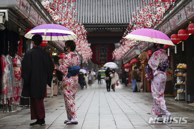 [도쿄=AP/뉴시스]12일 일본 도쿄 아사쿠사 지구의 한 쇼핑몰에서 마스크를 쓴 기모노 차림의 시민들이 걸어가고 있다. 코로나19 확산을 막기 위해 비상사태 선포 중인 도쿄도에서 11일 970명의 신규 확진자가 보고됐다. 2021.01.12.