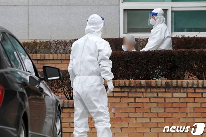 방역당국 관계자들이 코로나19 확진자를 이송하고 있다.  2021.1.3/뉴스1 © News1 황희규 기자