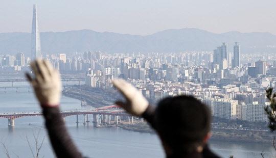 한 시민이 서울 매봉산에서 송파구, 강남구 일대 아파트 밀집 지역을 바라보고 있다. <연합뉴스>
