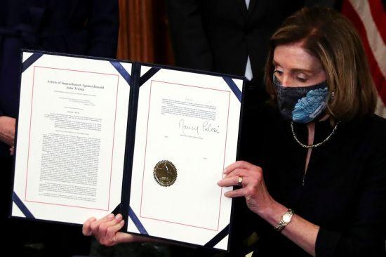 낸시 펠로시 하원의장이 서명한 트럼프 대통령 탄핵 소추안을 들어보이고 있다. [이미지출처=로이터연합뉴스]