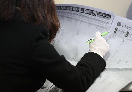 지난달 4일 서울 한 학원이 개최한 2021 대입전략 설명회에서 학부모가 정시모집 배치표를 살펴보고 있다. 연합뉴스