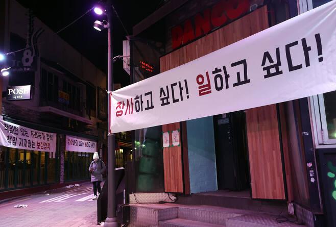 19일 오후 서울 이태원 거리에 오후 9시 이후 영업 제한 조치 등 정부의 정책에 항의하는 내용의 현수막이 걸려있는 모습 ⓒ 연합뉴스